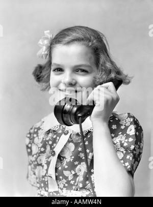 Années 1920 Années 1930 SMILING LITTLE GIRL DANS UNE ROBE D'IMPRESSION DE PARLER AU TÉLÉPHONE LOOKING AT CAMERA Banque D'Images