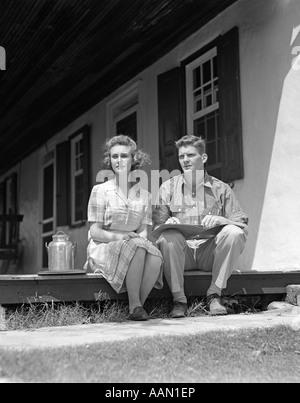 1940 HOMME FEMME COUPLE ASSIS À LA MAISON FERME PORCHE DE CÔTÉ GRAND LIVRE LES GENOUX de l'homme petite robe à carreaux Banque D'Images