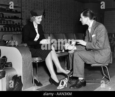 1930 VENDEUR DE CHAUSSURES FEMME AIDANT À essayer sur la paire de talons hauts dans le magasin de chaussures au Banque D'Images