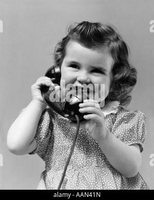 1930 LITTLE GIRL SMILING MONTRANT SES FOSSETTES TALKING ON TELEPHONE Banque D'Images