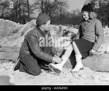 Années 1930 Années 1940 TEENAGE COUPLE IN KNIT CAPS & BOOTS GARÇON AGENOUILLÉ lier des patins à glace pour fille Banque D'Images