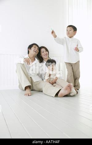 Fils jouant avec des bulles et les parents à regarder avec sourire. Banque D'Images