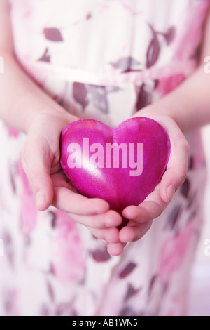 A girl holding a pink heart Banque D'Images