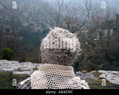 Femme portant chapeau laineux à sur une vallée boisée d'hiver Banque D'Images