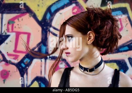 Portrait d'une fille aux cheveux rouges en face de graffitis Banque D'Images