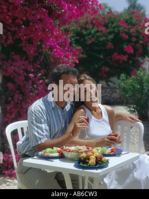 Jeune couple boire et manger en plein air sur une terrasse avec des fleurs des bougainvillées en arrière-plan