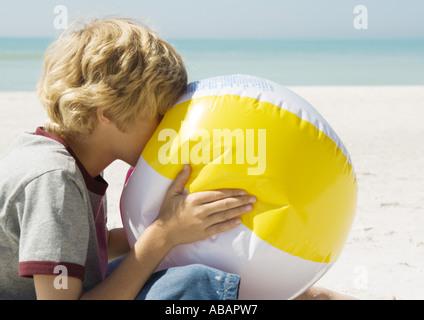 Boy Blowing up beach ball Banque D'Images