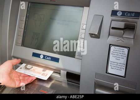 Distributeur automatique de billets trou dans le guichet bancaire retirer l'écran d'argent avec la main d'un retraité prenant des billets de 10 livres sterling. Angleterre Royaume-Uni Grande-Bretagne