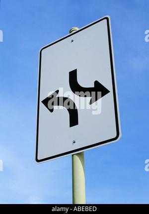 Signe de route avec deux flèches pointant dans des directions opposées Banque D'Images