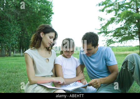 Girl reading book avec les parents, sitting on grass