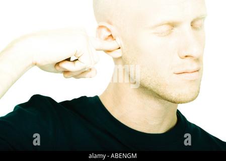 Jeune homme branché avec le doigt de l'oreille, les yeux fermés