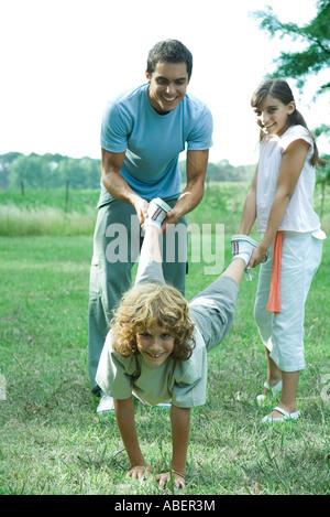 L'extérieur de la famille, père et sœur holding jambes du garçon comme brouette Banque D'Images