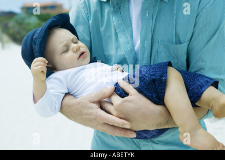 Man holding baby on beach Banque D'Images