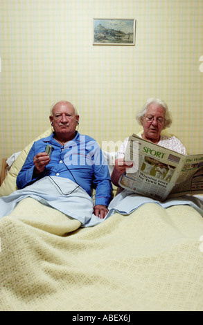 Senior couple in bed, woman reading newspaper Banque D'Images