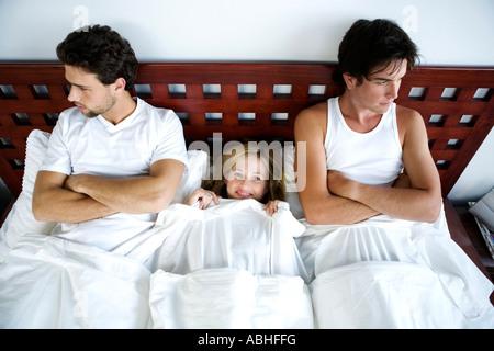 Young smiling woman in bed entre 2 hommes, les bras croisés Banque D'Images