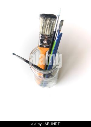 Groupe de divers outils artistiques et peintre dans une bouteille en verre sur un fond blanc Banque D'Images