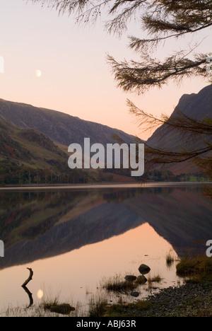 Les derniers rayons de soleil d'automne sur les montagnes au loin et le lever de lune qui se reflètent parfaitement Banque D'Images