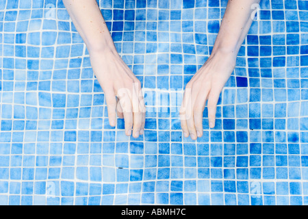 Mains de Woman in Swimming Pool Banque D'Images