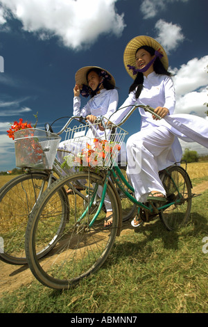 Deux jeunes femmes à chapeaux coniques et costumes traditionnels de la bicyclette à travers les rizières près de Banque D'Images