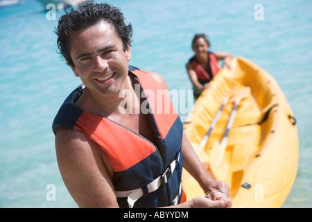 Couple tirant hors de l'eau en kayak Banque D'Images