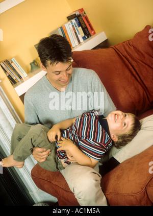 Père rude et jouant avec son fils à l'intérieur Banque D'Images