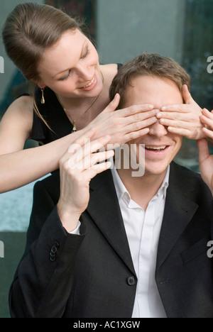 Femme couvrant les yeux de l'homme avec les mains Banque D'Images