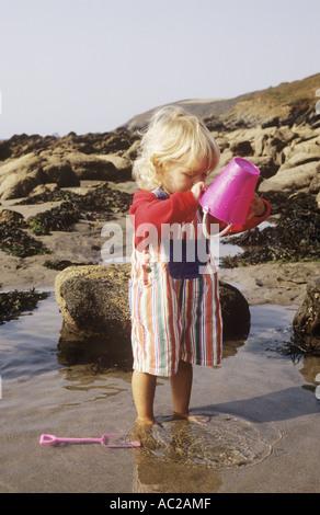 Jeune fille avec un seau et cosse dans une piscine dans les rochers sur une plage en Cornouailles au Royaume-Uni Banque D'Images