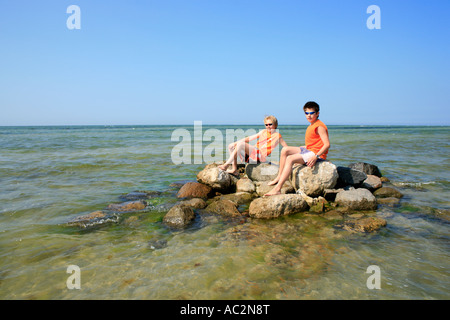 Deux jeunes garçons assis sur une île isolée de roches au large d'une plage de la mer Baltique Mecklembourg-Poméranie Banque D'Images