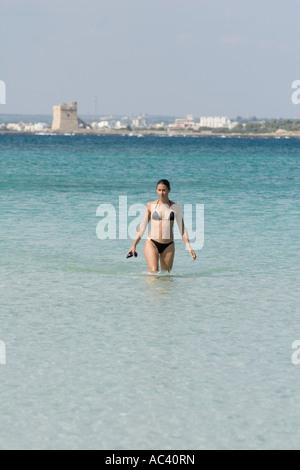 Young woman wading de mer avec lunettes de natation dans la main Banque D'Images