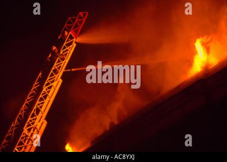 Pompiers Pompiers / Feu de combat et des flammes dans un bâtiment en feu avec le tuyau d'eau à partir d'une échelle aérienne