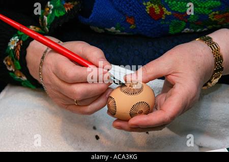 Femal peinture mains un œuf de pâques avec la cire pour la teinture en Hesse technique batik traditionnel Banque D'Images
