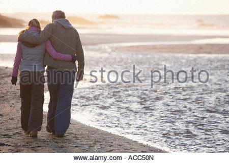 Heureusement couple embracing marchant sur la plage Banque D'Images