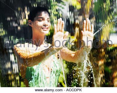 Femme en maillot de bain derrière une cascade Banque D'Images