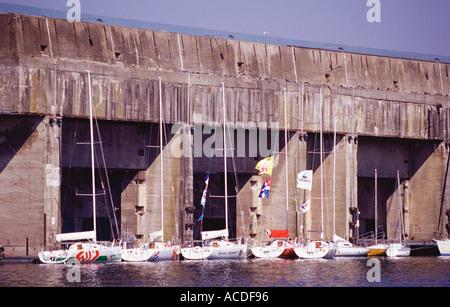 Racing yachts amarrés en face de la base sous-marine allemande géant construit à Saint Nazaire Bretagne France Banque D'Images