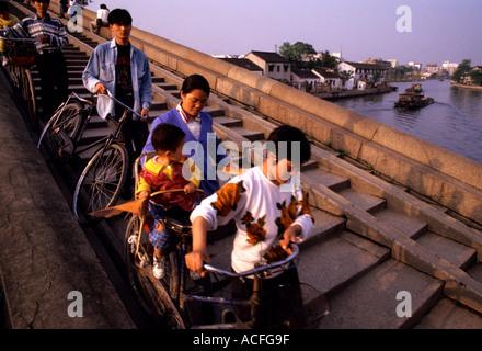 Suzhou Jiangsu Chine balades cyclistes leur vélo sur un pont en pierre voûtée de l'autre côté du Grand Canal Banque D'Images