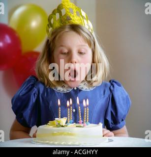 Célébration d'anniversaire pour un enfant de 6 ans fille blonde souffle les bougies sur son gâteau Banque D'Images