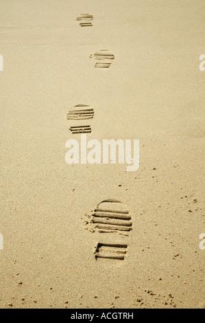 Une magnifique journée d'été à la plage de sable doré avec le bleu de l'océan venant dans et autour des traces de Banque D'Images