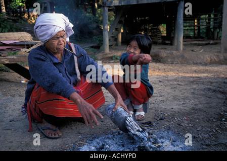 La Thaïlande Le parc national de Doi Inthanon vieille femme et sa petite-fille s'asseoir par un incendie le matin Banque D'Images