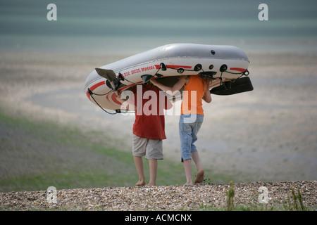 Les enfants sur la plage à marée basse en canot à la mer, Mersea Island, Essex, Angleterre, RU Banque D'Images