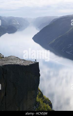 Walker debout sur Preikestolen, ou Pulpit Rock, au-dessus de Lysefjorden, Dale i Sunnfjord, Rogaland,. Banque D'Images