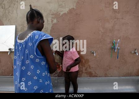 Une femme lave sa fille à un demandeur d'asile d'Afrique du Sud d'Israël composé Banque D'Images