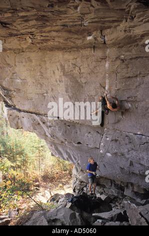 Male rock climber ascending falaise en surplomb Banque D'Images