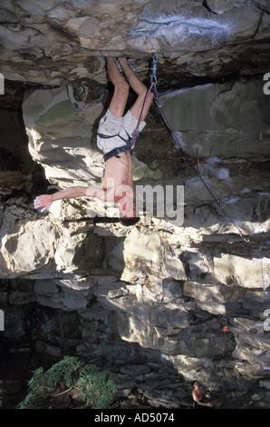 Male rock climber hanging from un toit dans une falaise en surplomb Banque D'Images