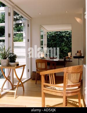 Fauteuil en bois et petite table sur parquet dans la salle à manger moderne blanc extension avec miroir au-dessus Banque D'Images