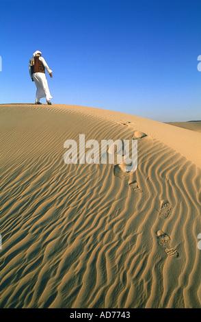 Egypte Le LYBIC DÉSERT ET L'oasis de Siwa, PRÈS DE LA MER DE SABLE D'ESCALADE UNE DUNE BÉDOUIN Banque D'Images