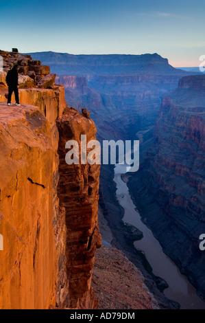 Personne debout au bord d'une falaise abrupte au-dessus de la rivière Colorado au lever de Toroweap Grand Canyon Banque D'Images