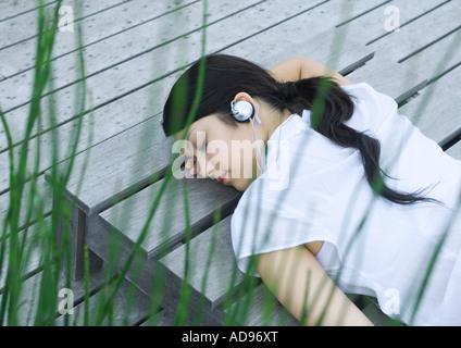 Femme couchée sur lame de listening to headphones Banque D'Images