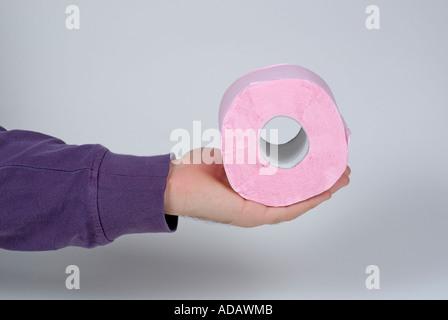 Main tenant un rouleau de papier toilette rose.