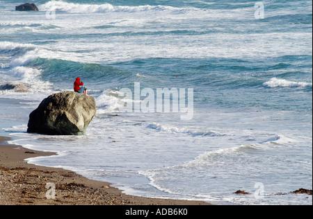 Ocean Watch. Un jeune homme est assis sur un rocher par l'océan pacifique à Carpinteria, en Californie Banque D'Images