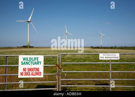 3 éoliennes on wind farm contre ciel nuageux bleu et vert avec des champs de trèfle porte cadenassée refuge d'oiseaux Banque D'Images